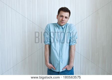 Caucasian Shy Young Man In Blue Shirt Standing Near Wall. Hands Hides In Pockets.