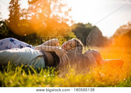 Young mixed race couple relaxing in grass - dreamy look