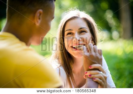 Young man feeding woman with chocolate outdoors in park