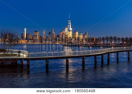 New York City Financial District skyscrapers at sunset and Hudson River from Hoboken promenade. Lower Manhattan skyline and pedestrian bridge from New Jersey