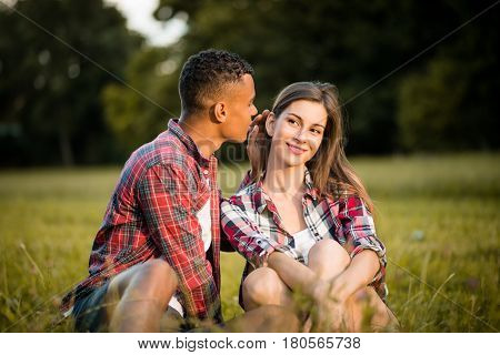 Young man whispering to her girlfriend - outdoor in nature