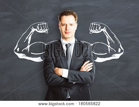 Confident businessman with drawn muscly hands on chalkboard background. Power concept