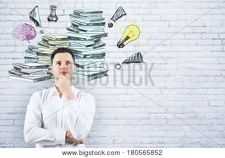 Thoughtful businessman on white brick background with drawn paperwork pile. Workload concept