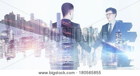 Businessmen shaking hands on abstract city background. Teamwork concept. Double exposure