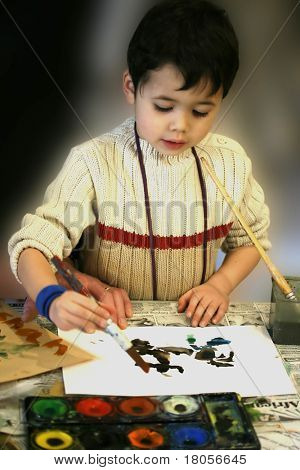 A young boy engross in his paintwork
