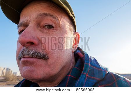 An Elderly Man With A Mustache Looks Suspiciously. Distortion Of The Proportions Of The Face.