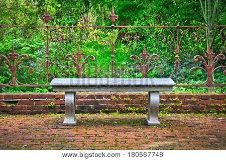 Old Bench in formal English garden with ornate wrought iron fence
