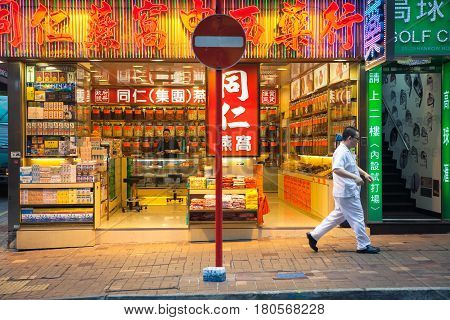 HONG KONG, CHINA - FEBRUARY 16: Man passes by neon-lighted traditional Chinese medicine store on February 16, 2014 in Hong Kong, China.