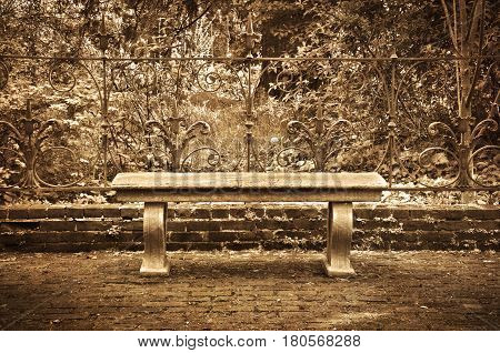 Old bench in formal English garden with sepia tone effect