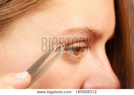 Woman plucking eyebrows depilating with tweezers closeup part of face. Girl tweezing eyebrows. poster
