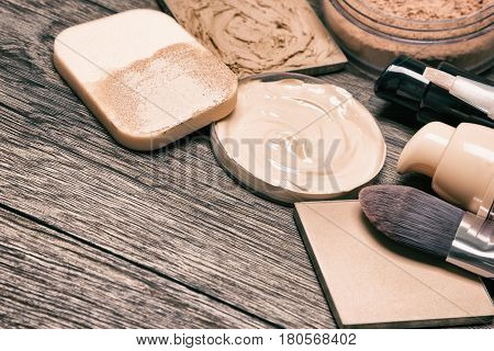 Essential products for face makeup: liquid foundation, concealer, powder. Selective focus, toned image with copy space