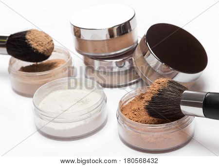 Jars of loose cosmetic powder different colors and shades with makeup brushes on light background. Shallow depth of field