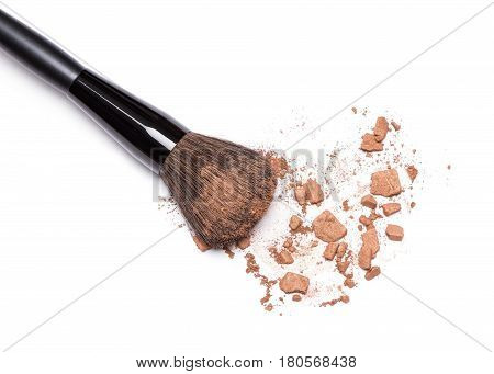 Close-up of crushed bronzing powder with makeup brush on white background. Bronzer for face contouring or creating tanned look