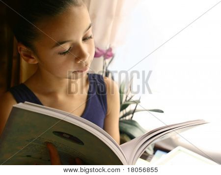 A young girl engross in her storybook, beautifully lit by the light from the window.