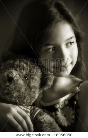 A young girl enjoying a quiet moment with her favourite cuddly toy. Rendered duotone suggestion of vintage photography.