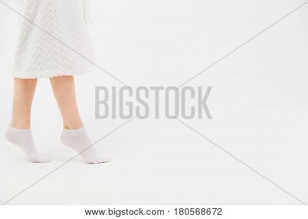 A girl in a white bathrobe and socks goes on socks after a shower. Close-up of beautiful female slender legs. Side view. Barefoot helth concept