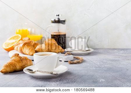 Healthy breakfast with coffee, croissants and orange juice on light gray background, selective focus, copy space.