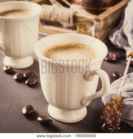 Two retro cups of coffee and old coffee pot on dark brown background. Retro style toned.