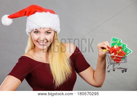 Xmas seasonal sales winter celebration concept. Happy woman wearing Santa Claus helper hat holding shopping basket cart with little christmas tree and gifts inside.