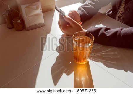 A girl is sitting in a cafe and looking into the phone drinking compote. Break during the working day healthy eating