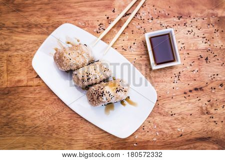 Sushi Onigiri with tuna and soy sauce on a white plate