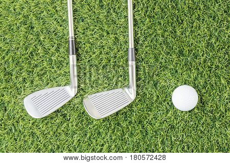 Sport objects related to golf equipment Golf club and golf ball on green grass