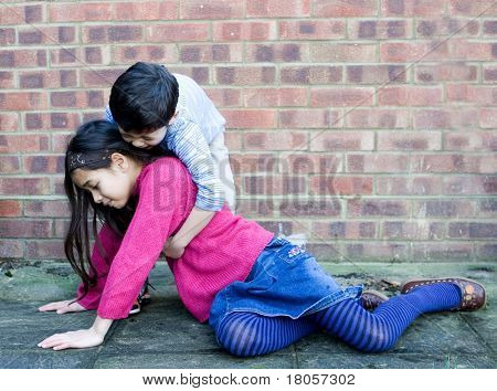 A young boy helping his sister up after she slips over.