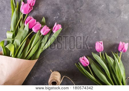 Pink tulips in a package of craft. Pink tulips on gray abstract background. Pink tulip. Tulips. Flowers. Flower background.. Pink tulip. Tulips. Flowers. Flower background. Flowers photo concept. Holidays photo concept. Copyspace