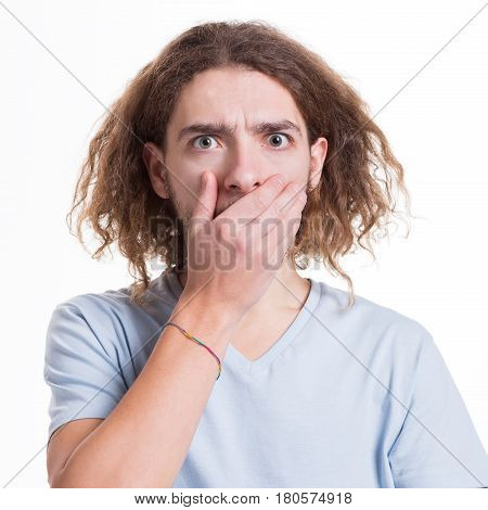 Keep silence. Gossip concept. Surprised man covering mouth with hand on white isolated studio background