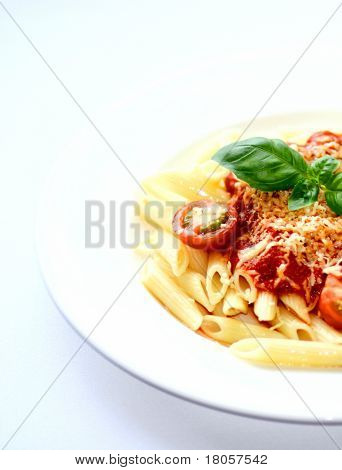 A plate of penne pasta tubes with rich tomato sauce and sprinkling of grated cheese, garnish with cherry tomatoes and sprig of basil