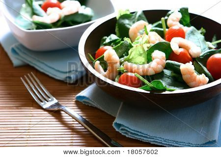 Bowls of fresh prawn salad with cherry tomatoes, baby spinach leaves and fresh salad leaves.