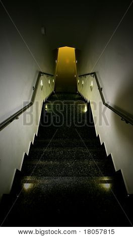 A walkway down a steep stairwell towards a source of light at the end. Concept of temptation and risk.