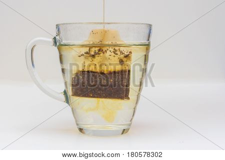 dipping tea bag into glass on white background