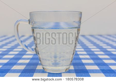tea glass of water standing on table with blue and white cloth