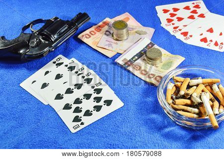 straight flush win poker game and gun with cigarette on blue velvet table