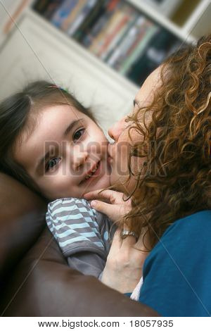 A beautiful little girl enjoys being kissed by her mother. Half saturation rendered with soft filter effect.