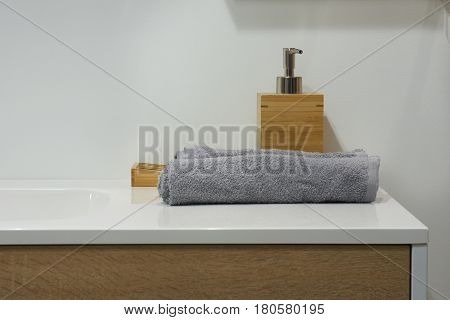 Liquid soap dispenser on white ceramic washbasin and two gray towels