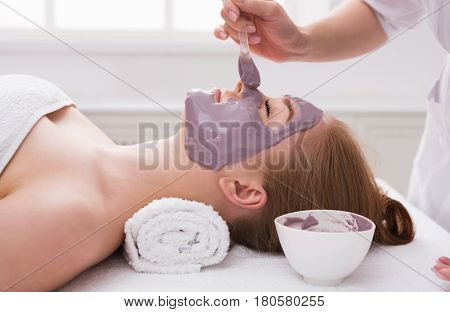 Face mask, spa beauty treatment, skincare. Woman getting facial nourishing mask by beautician at spa salon, side view, close-up