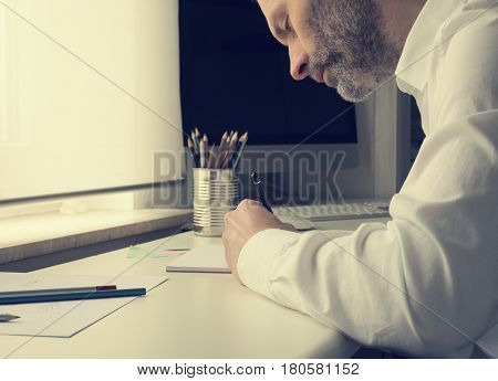 Man is drawing on a paper sheet creativity concept with natural light in an office
