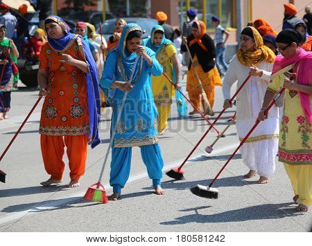 Vicenza, Vi, Italy - April 8, 2017: Women Sikh Religious Ceremony Sweep The Street With Brooms Durin