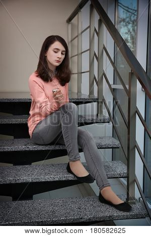 Teenage girl sitting on stairs and smoking