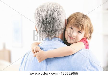 Girl embracing grand father at home