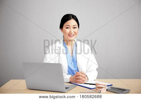 Pretty dentist working on laptop at workplace
