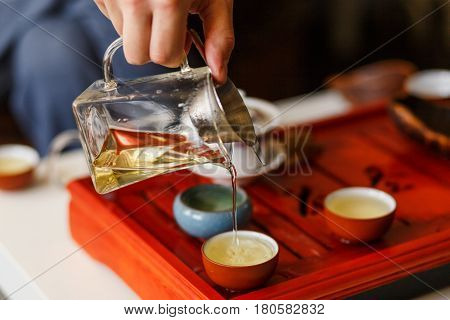 The Tea Ceremony. The Hands Of Man Pouring Tea.