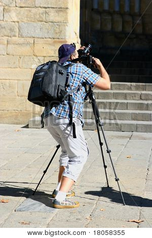 Male photographer with camera and tripod about to take a photo of a cathedral door.