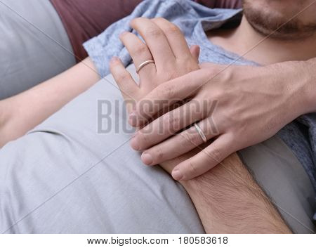 Two homosexuals lying on bed and holding each other hand