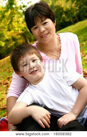 Thai mom with beautiful son from inter marriage, outdoor in the autumn park