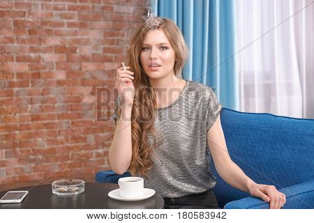 Young woman sitting on armchair and smoking in living room