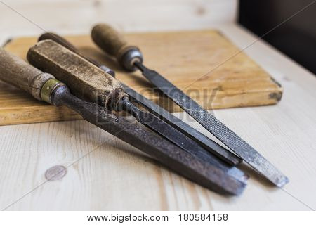 Vintage files and chisels lying on a diagonal on a brown wooden board on a light wooden table