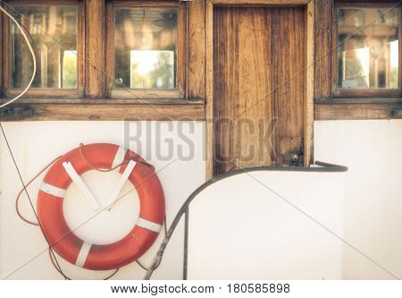 Orange lifebuoy on vintage white boat in port.